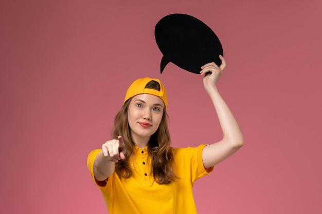 Corriere femminile di vista frontale in uniforme gialla e mantello che tiene segno nero sul lavoro uniforme di consegna di lavoro di servizio dell'azienda della parete rosa