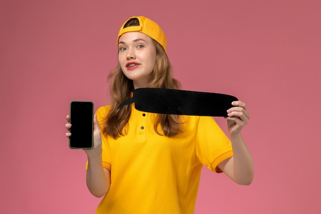 Front view female courier in yellow uniform and cape holding black sign and smartphone on pink wall company service worker delivery job uniform