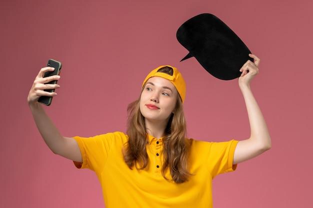 Corriere femminile di vista frontale in uniforme gialla e mantello che tiene segno nero e che prende una foto sull'uniforme di consegna del lavoratore di servizio dell'azienda della parete rosa