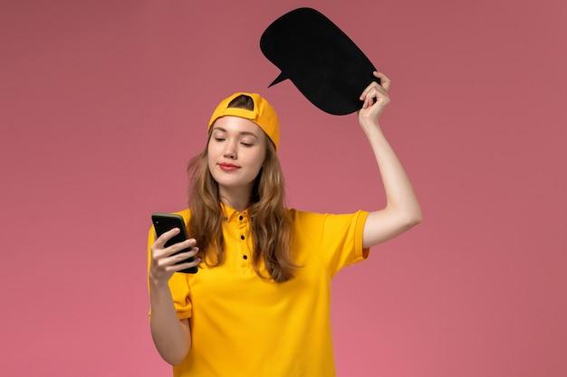 Corriere femminile di vista frontale in uniforme gialla e mantello che tiene segno nero e utilizzando il telefono sulla uniforme di consegna del lavoratore di servizio dell'azienda della parete rosa