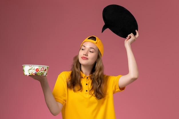 Corriere femminile di vista frontale in uniforme gialla e mantello che tiene segno nero con ciotola sulla società uniforme di consegna servizio parete rosa