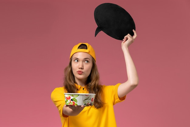 Front view female courier in yellow uniform and cape holding black sign with bowl on the pink wall service delivery uniform company