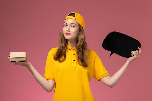 Corriere femminile di vista frontale in uniforme gialla e mantello che tiene segno nero con il pacchetto di cibo sull'uniforme di consegna di servizio dell'azienda della parete rosa