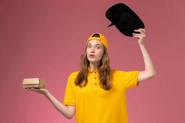 Corriere femminile di vista frontale in uniforme gialla e mantello che tiene segno nero con il pacchetto di cibo sulla uniforme di consegna del lavoratore di servizio dell'azienda della parete rosa