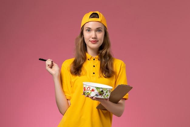 Corriere femminile di vista frontale in uniforme gialla e mantello che tiene la ciotola di consegna e il blocco note con la penna sul lavoratore dell'azienda dell'uniforme di consegna di servizio della parete rosa chiaro