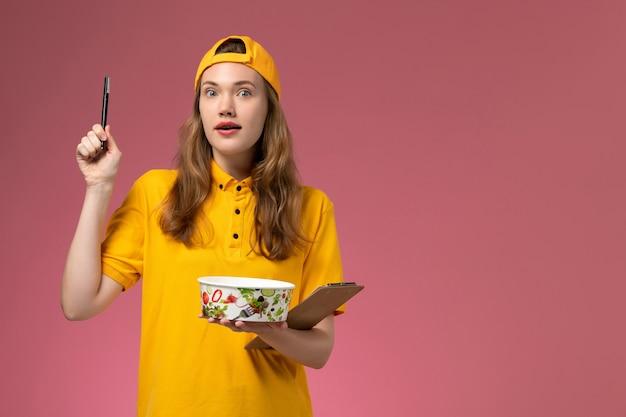 Corriere femminile di vista frontale in uniforme gialla e ciotola di consegna della tenuta del capo e blocco note con la penna sulla società dell'uniforme di consegna di servizio della parete rosa chiaro