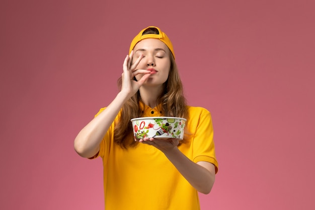 Front view female courier in yellow uniform and cape holding delivery bowl on the pink wall service delivery uniform company job work