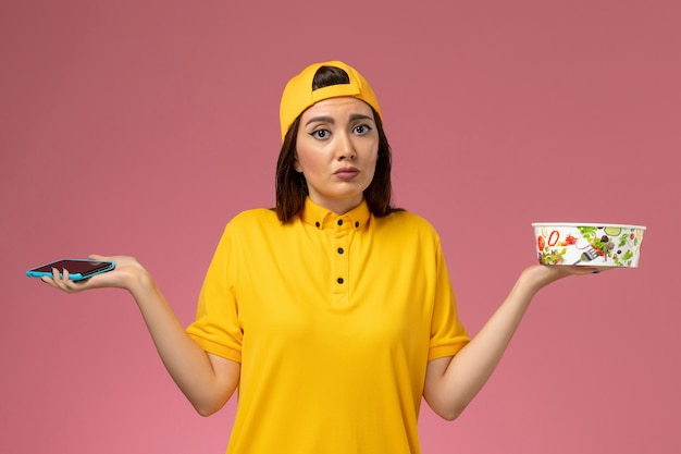 Front view female courier in yellow uniform and cape holding delivery bowl and smartphone on light-pink wall service uniform delivery