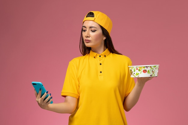 Front view female courier in yellow uniform and cape holding delivery bowl and using a phone on the light pink desk company service uniform delivery job work