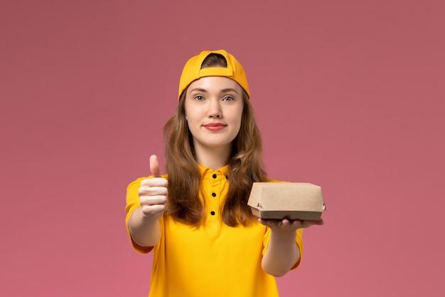 Corriere femminile di vista frontale in uniforme gialla e mantello che tiene il pacchetto di cibo di consegna sulla società uniforme di lavoro di consegna di servizio della parete rosa