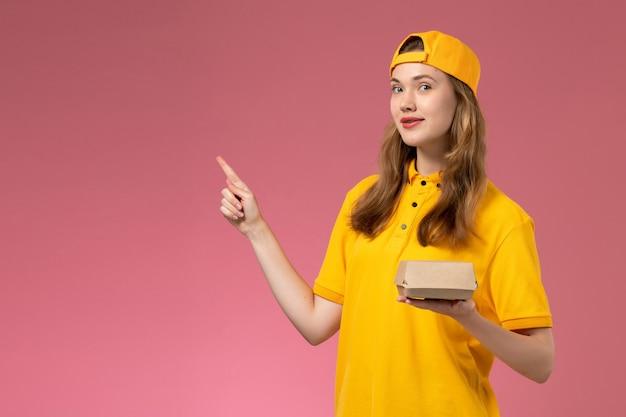 Corriere femminile di vista frontale in uniforme gialla e capo che tiene il pacchetto dell'alimento di consegna sul lavoro della ragazza dell'azienda dell'uniforme di consegna di servizio della parete rosa
