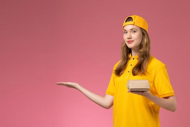 Corriere femminile di vista frontale in uniforme gialla e mantello che tiene il pacchetto di cibo di consegna sul lavoro di lavoro dell'azienda uniforme di consegna di servizio della parete rosa