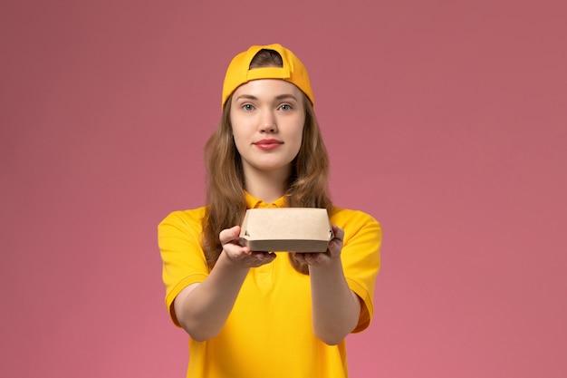 Corriere femminile di vista frontale in uniforme gialla e mantello che tiene il pacchetto di cibo di consegna sulla parete rosa servizio uniforme di consegna azienda lavoro lavoratore ragazza lavoro