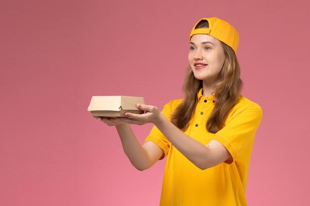 Corriere femminile di vista frontale in uniforme gialla e mantello che tiene il pacchetto dell'alimento di consegna sulla ragazza dell'operaio di lavoro dell'azienda uniforme di consegna di servizio della parete rosa