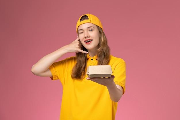 Corriere femminile di vista frontale in uniforme gialla e mantello che tiene il pacchetto dell'alimento di consegna sul lavoratore di lavoro dell'azienda uniforme di consegna di servizio della parete rosa