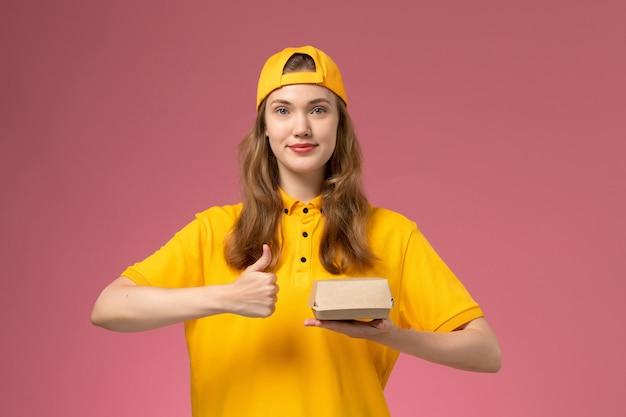 Corriere femminile di vista frontale in uniforme gialla e mantello che tiene il pacchetto di cibo di consegna sul lavoro dell'azienda uniforme di consegna di servizio della parete rosa