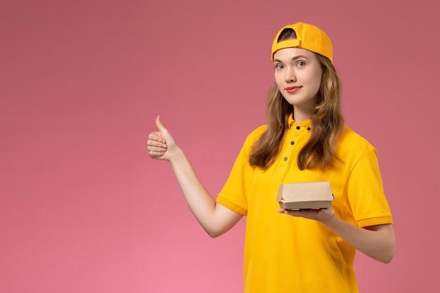 Corriere femminile di vista frontale in uniforme gialla e mantello che tiene il pacchetto di cibo di consegna sul lavoro dell'operaio dell'azienda dell'uniforme di consegna di servizio della parete rosa