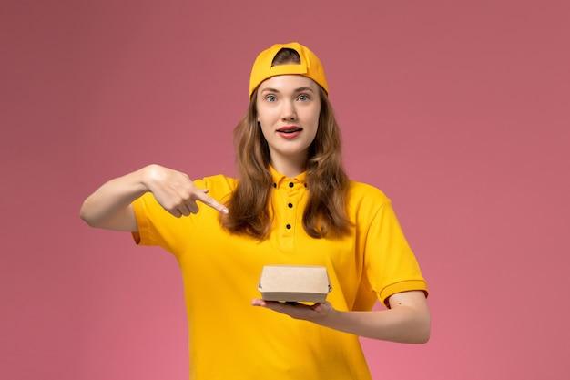 Corriere femminile di vista frontale in uniforme gialla e mantello che tiene il pacchetto di cibo di consegna sul lavoratore dell'azienda uniforme di consegna di servizio della parete rosa