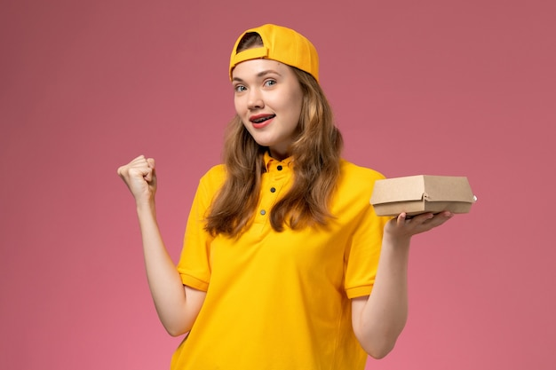 Front view female courier in yellow uniform and cape holding delivery food package on pink wall service delivery uniform job