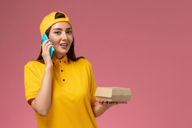 Corriere femminile di vista frontale in uniforme gialla e mantello che tiene il pacchetto di cibo e parla al telefono sulla ragazza di consegna uniforme di servizio della società di parete rosa chiaro