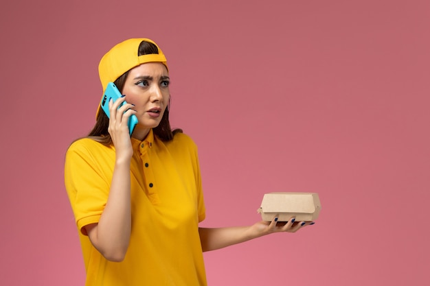 Front view female courier in yellow uniform and cape holding food package and talking on the phone on the light-pink wall company service uniform delivery job