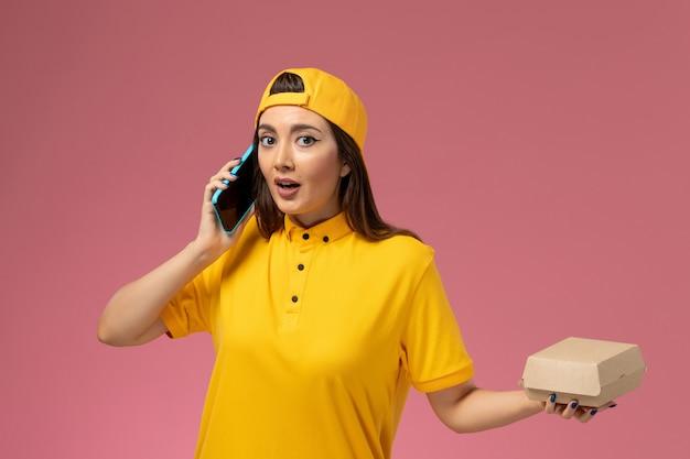 Corriere femminile di vista frontale in uniforme gialla e mantello che tiene il pacchetto di cibo e parla al telefono sul lavoro di consegna dell'uniforme di servizio della società della parete rosa chiaro