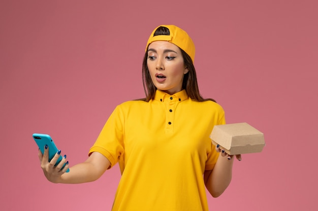 Corriere femminile di vista frontale in uniforme gialla e mantello che tiene il pacchetto di cibo e utilizzando un telefono sul lavoratore di consegna uniforme di servizio della società della parete rosa chiaro