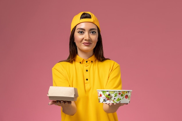 Corriere femminile di vista frontale in uniforme gialla e mantello che tiene il pacchetto di cibo con la ciotola sul lavoro di consegna dell'uniforme di servizio dell'azienda della parete rosa chiaro