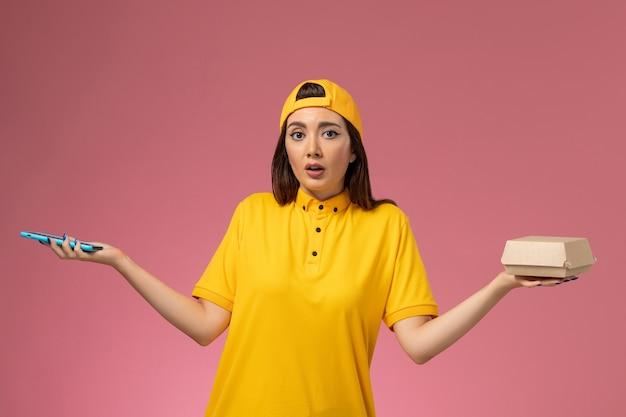 Corriere femminile di vista frontale in uniforme gialla e mantello che tiene il pacchetto di cibo con il suo telefono di lavoro sulla consegna dell'uniforme di servizio dell'azienda della parete rosa chiaro