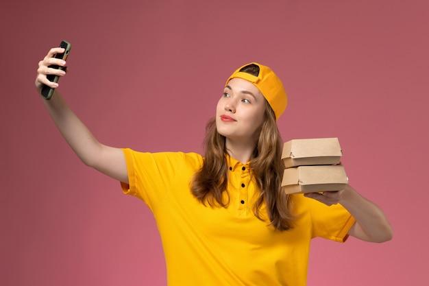 Corriere femminile di vista frontale in uniforme gialla e mantello che tiene i pacchetti di cibo che scatta una foto sul lavoro dell'uniforme di consegna di servizio dell'azienda della parete rosa