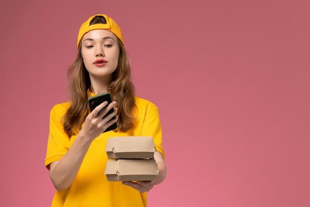 Corriere femminile di vista frontale in uniforme gialla e mantello che tiene i pacchetti di cibo parlando al telefono sul lavoro uniforme di consegna del servizio di azienda di muro rosa