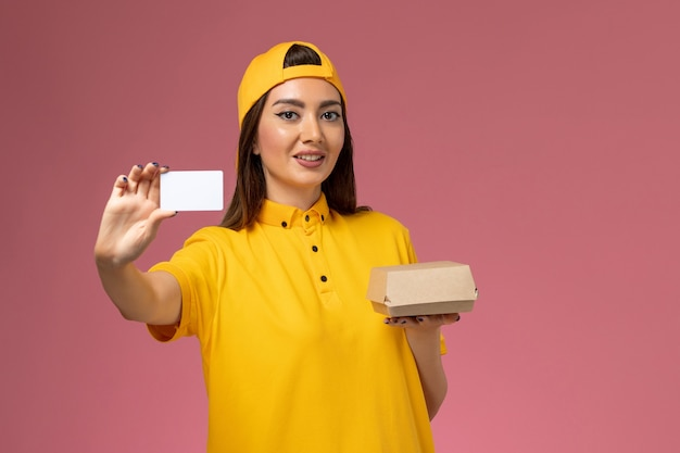 Front view female courier in yellow uniform and cape holding little delivery food package and card on light-pink wall service job work uniform delivery company