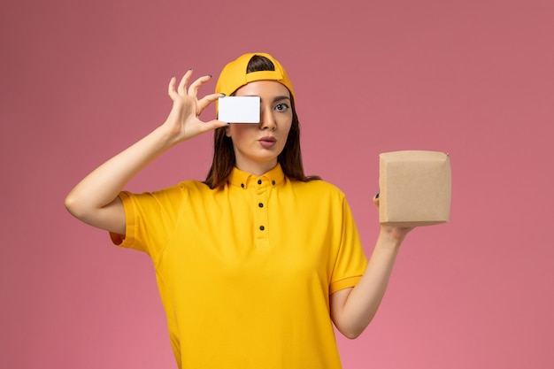 Front view female courier in yellow uniform and cape holding little delivery food package and card on light-pink wall service uniform delivery company girl job