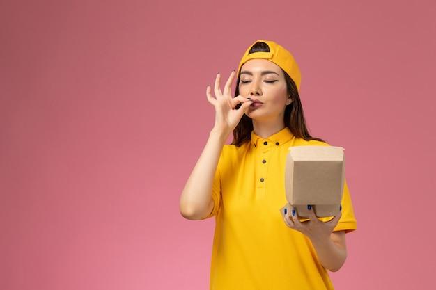 Corriere femminile di vista frontale in uniforme gialla e mantello che tiene piccolo pacchetto di cibo di consegna sul lavoro della ragazza della società di consegna uniforme di servizio della parete rosa chiaro