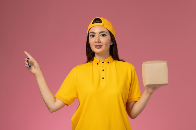 Front view female courier in yellow uniform and cape holding little delivery food package on light-pink wall uniform service delivery company job