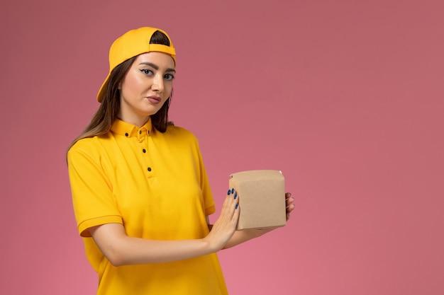 Corriere femminile di vista frontale in uniforme gialla e mantello che tiene piccolo pacchetto dell'alimento di consegna sulla società di consegna del lavoratore di servizio dell'uniforme della parete rosa chiaro