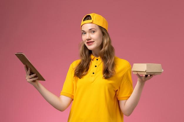 Corriere femminile di vista frontale in uniforme gialla e mantello che tiene poco pacchetto di cibo di consegna e blocco note sul lavoratore dell'uniforme di consegna di servizio della parete rosa chiaro