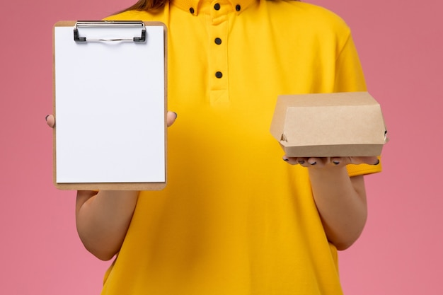 Front view female courier in yellow uniform and cape holding little delivery food package and notepad on the light-pink wall service uniform delivery job