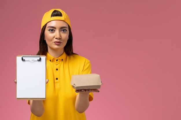Front view female courier in yellow uniform and cape holding little delivery food package and notepad on light-pink wall service uniform delivery worker
