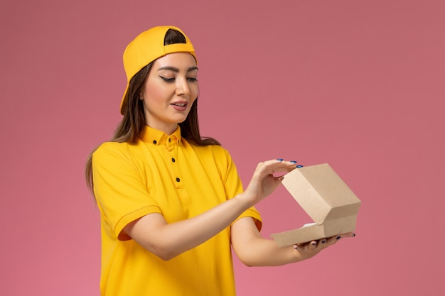 Front view female courier in yellow uniform and cape holding little delivery food package and opening it on pink wall uniform service delivery company
