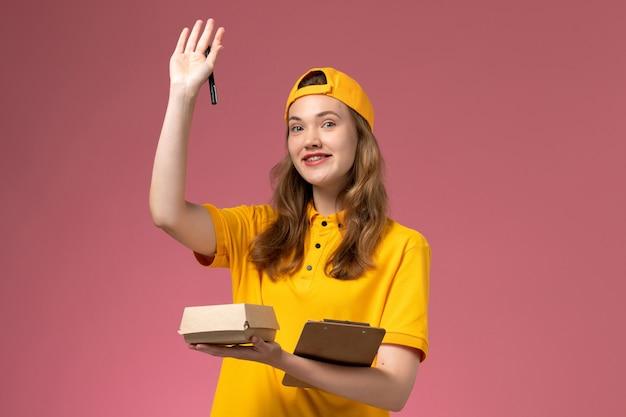 Corriere femminile di vista frontale in uniforme gialla e mantello che tiene poca penna del pacchetto di cibo di consegna e blocco note sull'uniforme di consegna di servizio della parete rosa chiaro