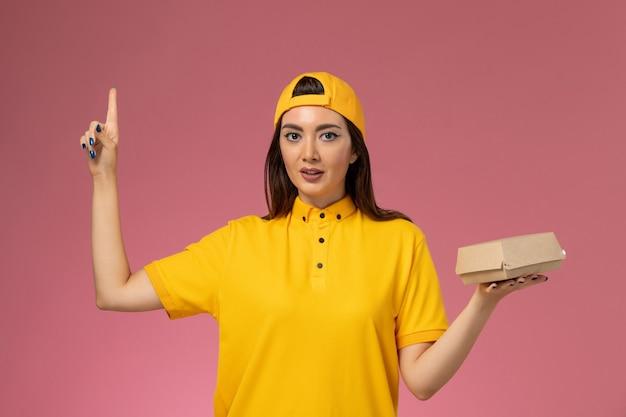 Corriere femminile di vista frontale in uniforme gialla e mantello che tiene piccolo pacchetto di cibo di consegna sul lavoratore ragazza della società di consegna di servizio uniforme della parete rosa