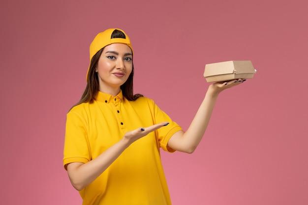 Corriere femminile di vista frontale in uniforme gialla e mantello che tiene piccolo pacchetto di cibo di consegna sulla ragazza della società di consegna di servizio uniforme della parete rosa