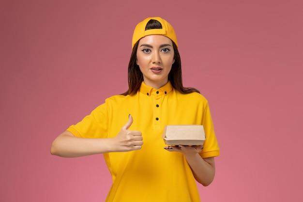 Corriere femminile di vista frontale in uniforme gialla e mantello che tiene poco pacchetto di cibo di consegna sul lavoro dell'operaio di lavoro dell'azienda di consegna di servizio uniforme della parete rosa