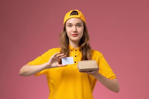 Corriere femminile di vista frontale in uniforme gialla e mantello che tiene piccolo pacchetto di cibo di consegna e carta di plastica sul lavoratore uniforme di consegna di servizio di lavoro della parete rosa