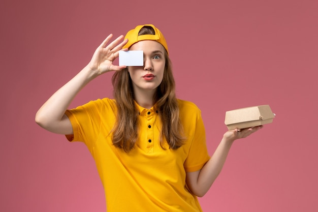 Front view female courier in yellow uniform and cape holding little delivery food package and plastic card on pink wall job service delivery uniform