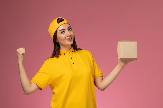 Corriere femminile di vista frontale in uniforme gialla e mantello che tiene il piccolo pacchetto di cibo di consegna che si rallegra sulla società di consegna di servizio uniforme della parete rosa chiaro
