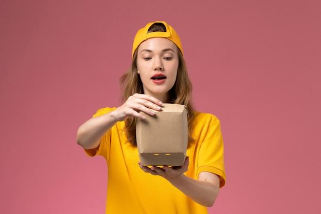 Corriere femminile di vista frontale in uniforme gialla e mantello che tiene piccoli pacchetti di cibo di consegna sull'uniforme di consegna di servizio della parete rosa chiaro