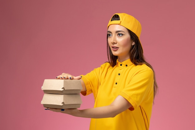Front view female courier in yellow uniform and cape holding little delivery food packages on the light-pink wall service uniform delivery girl work