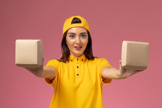 Corriere femminile di vista frontale in uniforme gialla e mantello che tiene piccoli pacchi di cibo di consegna sulla consegna uniforme di servizio della parete rosa chiaro